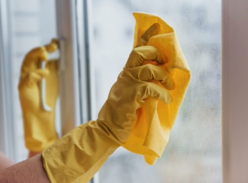 Housewife in yellow uniform cleaning windows. House renovation conception